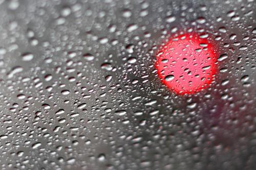 Regentropfen auf der Windschutzscheibe, rote Ampel im Bokeh